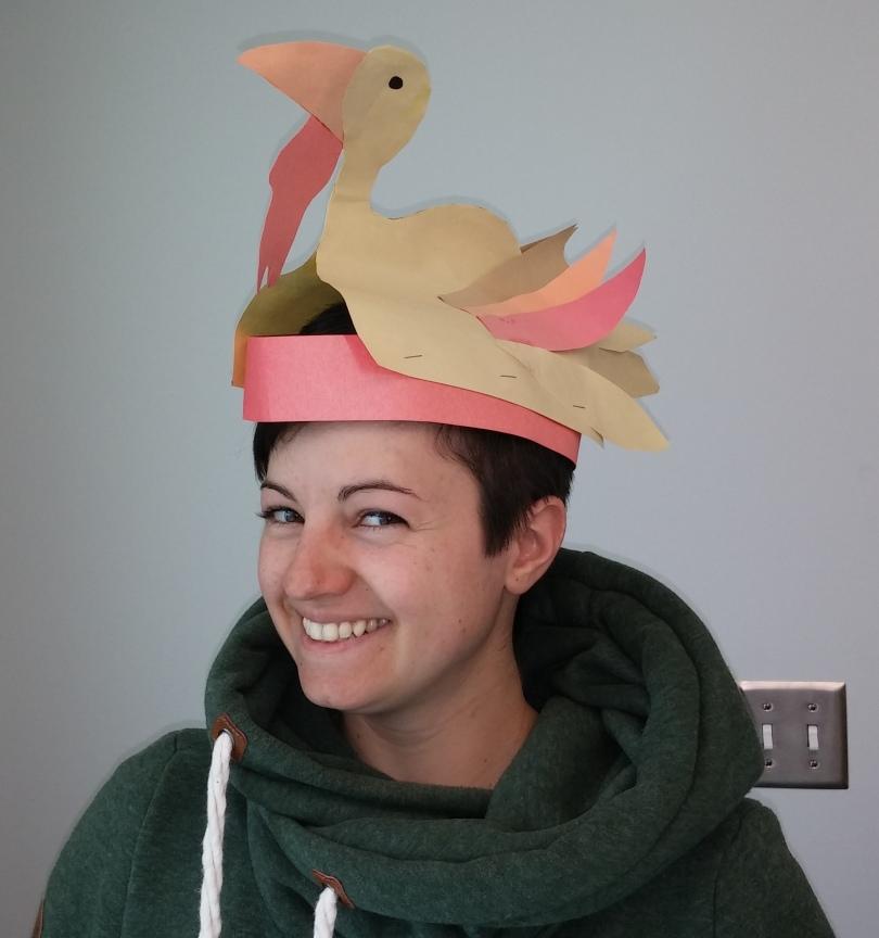 Sue wearing a paper hat shaped like a turkey.