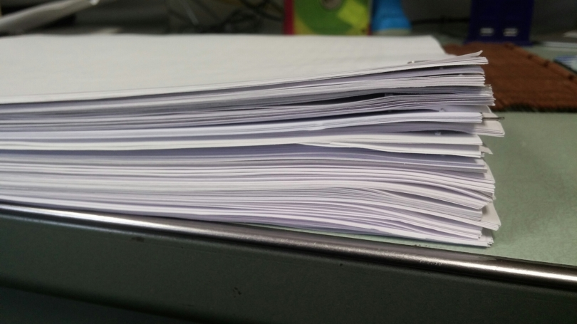 A stack of papers facedown on a table.