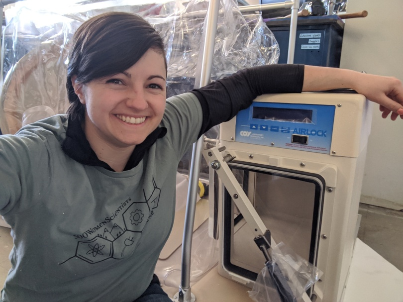 Picture of a woman smiling and hanging an arm off of a piece of lab equipment. She is wearing an olive green 500 Women Scientists t-shirt over a black collared long-sleeved shirt.