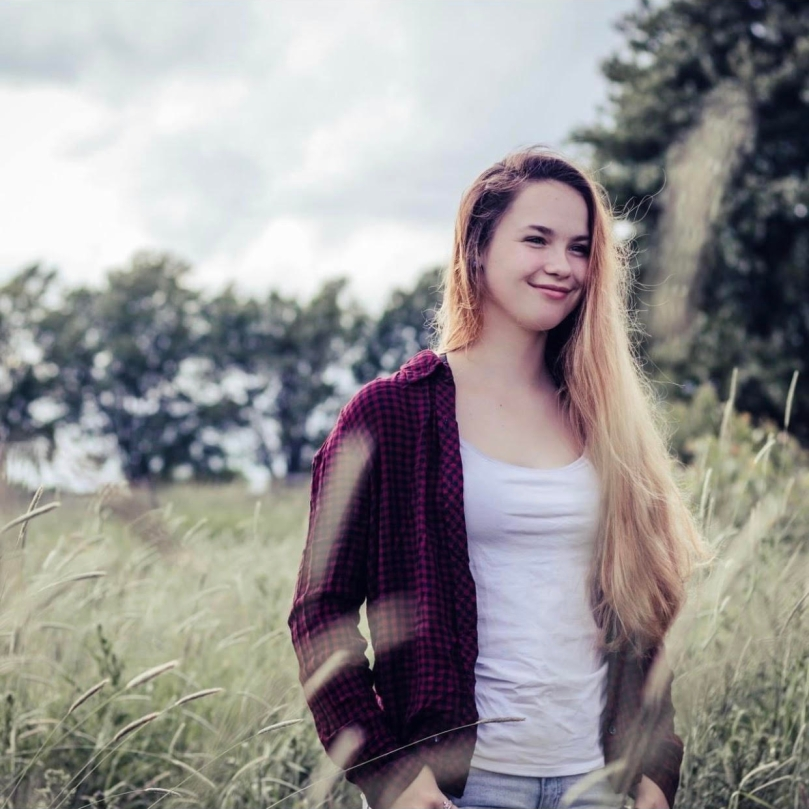 A blonde woman wearing a white tank top, and unzipped red hoodie, and jeans, while standing in a field of tall grass with trees in the background.